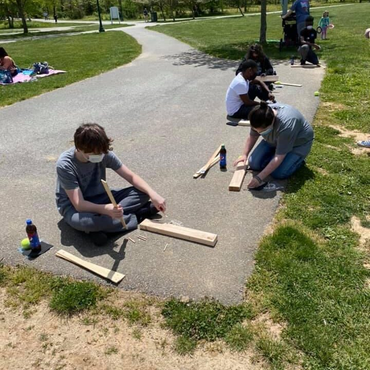 Kids outside building with wood.