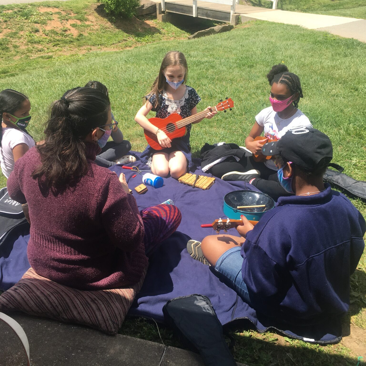 Kids outside for music class playing instruments in a circle